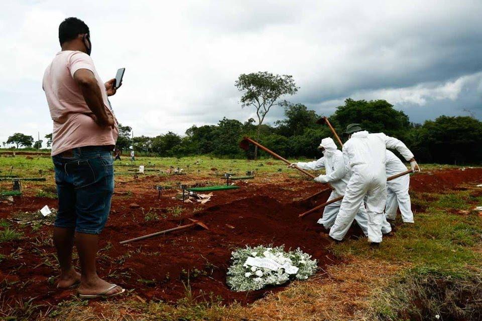 coveiros de cemitério municipal, em goiânia, goiás, enterram vítima de covid-19. rotina cansativa